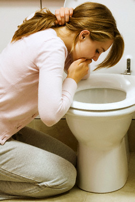 Girl Vomiting into Toilet Bowl